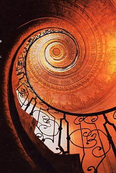 STUNNING Spiral stair.  Classical Architecture.  Wrought Iron railing.  European Design.  Beautiful Orange lighting.  #Interior-Architecture