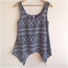 """Tribal print shark bite hem tank Super cute top to wear on its own or layered! Black and white print. Can't find the fabric/care tag but it feel like polyester, does not stretch. Measures 17"""" from underarm to underarm and 30"""" long at the longest point. Excellent condition! love on a hanger Tops Tank Tops"""