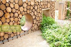 'Narratives of Nature' garden with reclaimed log wall and moon gate. Planting includes ferns, Geranium sylvaticum, Luzula nivea, Atriplex hortensis, Umbilicus rupestris and Betula pubescens. Future gardens, St Albans, Herts