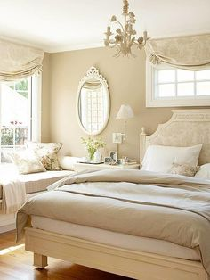 Many cottage-style decorating ideas pass on color for a mix of warm, cozy neutrals. Soft taupe and cream toile fabric adorns the windows and headboard in this bedroom. An iron chandelier painted the same mocha color as the walls and a carved wooden mirror finished with off-white paint match the romance of the fabric.