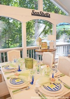 Stripes, polka dots, and solid flatware patterns. Love it. A Summer Porch With A Beach Themed Table Setting Tablescape