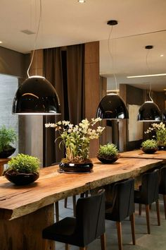 A dining table made of raw edged wood with black chairs & modern lighting.