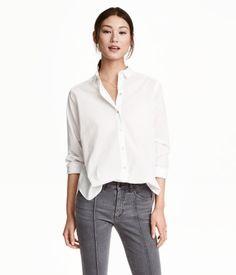 Hvit. En langermet, rett skåret skjorte i vevd bomullskvalitet. Skjorten har turn down-krage og knapping foran med perlemorknapper. Noe lengre bakstykke.