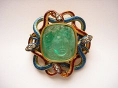 Cameo; emerald, head of Medusa facing; mounted in modern enamelled gold clasp representing four interlaced serpents with three diamonds set into each of their heads. 18 century