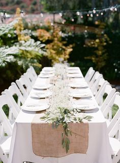 Burlap table runners and DIY flower arrangements made for a natural setting.  Source: Glitter Guide