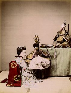 """A Maiko with Hina Matsuri Dolls 1890s. Photograph number 252 """"Girl"""" by the Kusakabe Kimbei Studio, showing a Maiko (Apprentice Geisha) arranging two large Dairi-bina (Lord and Lady) dolls for the annual Hina Matsuri (Festival of Dolls). The Dairi-bina dolls are the most important of all the Hina-ningyō (Hina Dolls), representing an Imperial Lord and Lady dressed in silken court robes, although they are often mistakenly referred to as Emperor and Empress Dolls."""