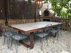 Mesa de exterior de hierro oxidado y baldosas.