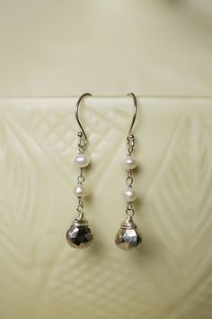 """A dangle cluster of pyrite is suspended by freshwater pearl on sterling silver. Pyrite, freshwater pearl Sterling silver earwires 1.5"""""""" long Individually handcrafted in our design studio"""