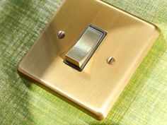 Victorian switchplate in antique brass with rocker switch and black interiors.