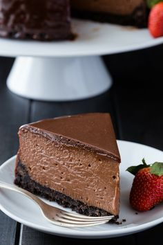 A slice of creamy nutella cheesecake on a white plate with a strawberry sitting next to it.
