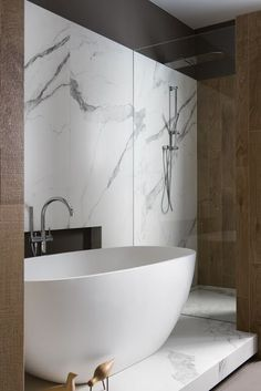 Super simple yet so sophisticated. Free standing tub on a bed full of marble Modern Bathroom Design by Minosa
