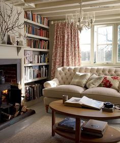 Light painted touches. Light soft. Dark fireplace. Pained beams, light rug. Light coloured walls. Red accents. Sanded floors