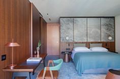 In the bedrooms of this hotel, Patricia Urquiola assembled earth-toned furniture with splashes of pastel pink and bolder shades of green.
