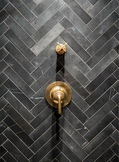 black herringbone tile, brass fixtures