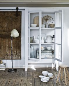White cupboard in a natural looking room with old wooden floors | white tableware | #mijnservies