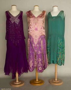 "THREE JEWELED SILK DRESSES, 1925-1934 2 mid 1920s beaded flapper dresses: 1 turquoise, aqua, seafoam green & silver beading, fair; 1 pink & magenta embroidered & beaded dress, label ""Eugenie et Juliette Paris"", poor; 1 early-mid 1930s purple, pearl & rhinestone studded pearl & rhinestone studded bodice, fair, all fragile. Front"