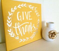 Give thanks- 12x12 hand painted, hand lettered sign  Canvas colors- yellow, orange, black, and white Lettering/wreath colors- 14 karat gold leaf,
