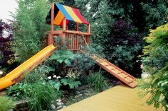 Treehouse for kids with sliding board, colorful yellow painted deck, garden plants, bamboo, childrens garden in backyard landscaping, family backyard garden