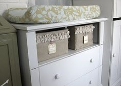 Dresser with the top drawer taken out to be basket place. Then put a baby-holding cushion on top and it is a dresser, too!