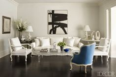 In this stylish Southampton home, all-white furniture is complemented by one chair's bright pop of blue. The Belgian linen-covered sofa is by Démiurge, the bergère is upholstered in a glazed linen by Rogers & Goffigon and the cocktail table is by Jansen. The vintage plaster lamps were made for Miami Beach's Eden Roc hotel.