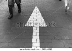 Arrow straight on pavement walking street with walking people wear jeans fashion vintage black and white - stock photo