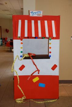 """DIY ticket booth - the big box came from a moving van company store & was painted or wrapped with red & white paper! The awning was a piece of cardboard painted to match the rest of the booth while the string of bright """"lights"""" are Christmas tree ornaments!"""