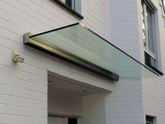 Edelstahlvordach Paderborn ein Echtglas Haustürvordach wo das Glas von einer Wandklemmleiste gehalten wird.
