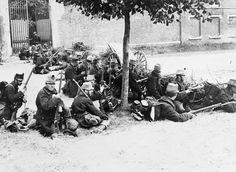 GERMAN INVASION BELGIUM AUGUST 1914 (Q 53206) Belgian soldiers sit behind a barricade armed with rifles in a street in Louvain on 20 August 1914 during the retreat to Antwerp.