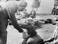 A woman inmate of Belsen concentration camp kisses the hand of Army Film & Photographic Unit cameraman Lieutenant Martyn Wilson on liberation.