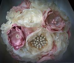 BUQUÊ ROMÂNTICO VINTAGE <br> <br>O buquê é composto de brochinhos, missangas peroladas, rendas, tules, strass, cristais, flores de tecidos nobres, ou qualquer outro adereço a gosto da noiva. Totalmente romântico. <br> <br>ENCOMENDE O SEU PERSONALIZADO. <br> <br>Pode ser feito em outras cores, com detalhes que combinem com o vestido da noiva ou com o casamento em geral. <br> <br>Buquê de flores de diferentes tecidos, com fino acabamento no cabo em cetim, renda e strass, confeccionado com…
