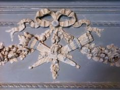 Typical Louis XVI motif; bow w/ ends flying off, swags & crossed torch & quiver of arrows. Very soft colors.
