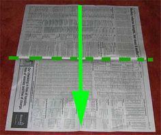 3. El doblez mas corto en el periódico debería ahora estar en posición vertical. Agarra una de las esquinas superiores y dóblala hacia abajo a lo largo de la línea central, creando un pliegue diagonal.