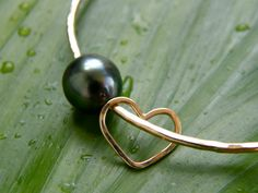 Love the pearl and heart combo https://www.etsy.com/listing/156519853/14kt-gold-filled-tahitian-pearl-bangle-w