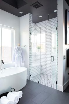 This luxurious master bath with high-tech features for the ultimate pampering experience has a classic black-and-white color scheme that was given a fresh spin with dueling tile patterns.