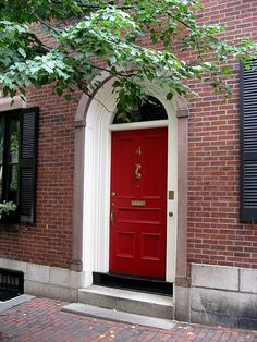 rich red front door, white trim, black shutters on brick