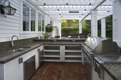 Outdoor kitchen with shelving and stucco base. Grill that runs from counter to floor.