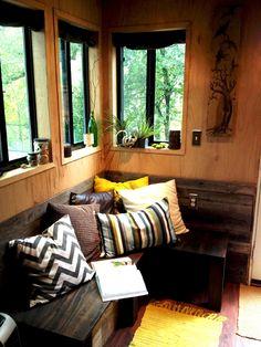 """O """"living"""" serve como área de conviência, leitura e escritório e foi inspirado na natureza. Neste cantinho, o banco de madeira escura recebe confortáveis almofadas coloridas. As janelas não só emolduram a paisagem, como recebem vasos com pequenas plantas ornamentais"""