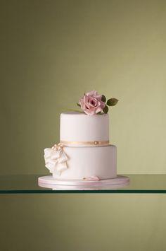 Bolo de casamento de dois andares com detalhe de laços e uma rosa