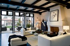 Living room in a Spanish revival home with exposed painted black beams, a grand fireplace, a jute rug, two white sofas and a large tufted ottoman