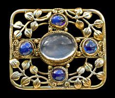 ARTIFICERS' GUILD 1901-1942 Attrib.  Arts & Crafts Brooch   Gold, moonstone & sapphire   Length: 2.2 cm Width: 2.7 cm (0.8 in x 1 in)   English. Circa 1905