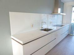 Witte glazen keuken achterwand staat mooi op een gekleurde muur