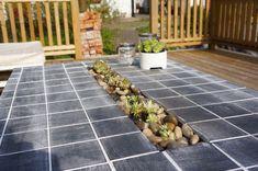 LindisPlace - Mitt i bordet så byggde jag en låda där jag har planterat taklökväxter och dekorerat med sten (från Biltema för den som undrar) :o) Innan jag planterade växterna så häftade jag fast en bit presening för att inte jorden skulle läcka ut i springorna. Jag klippte sedan några små hål i den för att vattnet ska kunna läcka ut och för att undvika översvämning när det regnar mycket. Jag fyllde sedan med lecakulor och jord, planterade mina taklökar och dekorerade med fina runda stenar.