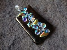 """Hytop"" - This fused glass pendant is one I made with dichroic glass pieces. ""Dichro"" is often defined as glass having multiple micro-layers of metal oxides which gives the glass a wide range of optical effects. It measures about 1-3/4"" long and about 1-1/4"" wide. I'll send a 16""-18"" black flocked/velvety cord along so it may be worn immediately.  $50.  Deep Fried Kudzu - DFK Jewelry Designs"
