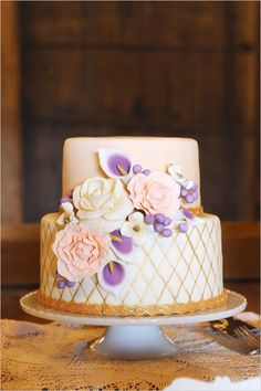 white wedding cake detailed with pink and purple flowers