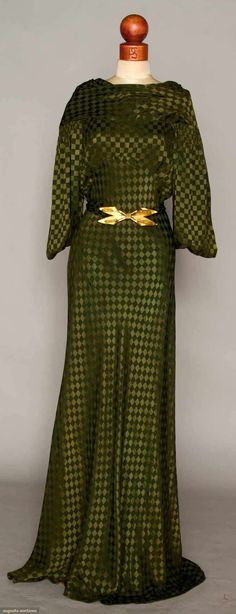 Olive Green Silk Evening Gown, Mid 1930s. Woven checkerboard pattern in satin & crepe squares, bias cut, kimono sleeves, high front neck, V back w/ key hole opening below, self fabric belt w/ brass buckle.