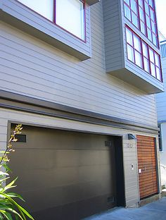 Twin Peaks Condo Building: A Semi-Industrial Look  The dark trim and garage color, and warm wood-slatted front door ground the building, offering a sense of support and solidity underneath the overhanging windows. San Francisco, Ca.  http://www.artifactorystudio.com/work/portfolio_color/col_more/gallery_col_cor_b.html