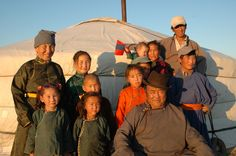 Mongolian people outside what looks like a house with their family, this shows exactly the kind of clothes that they wear.