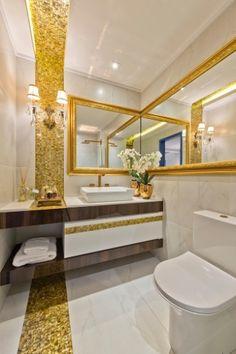 Dourado - Para criar uma atmosfera luxuosa neste banheiro, a arquiteta Tatielly Zammar combinou o tradicional revestimento branco com faixas de pastilhas douradas (Pastilhart Revestimentos). O espelho amplia o espaço e a moldura clássica dá o requinte necessário