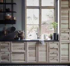 Cuisine avec portes et façades de tiroir en frêne naturel, poignées métalliques et comptoirs noirs, effet minéral.