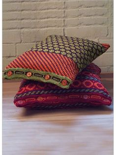 The designer drew inspiration for these brightly colored, multi-patterned pillows from embroidered motifs on the richly decorated textiles from the Kutch region of India. She uses a crisp cotton yarn in colors of eggplant, sage, and fresh chiles. The b